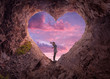 canvas print picture - Young woman in heart shape cave towards the beautiful sky