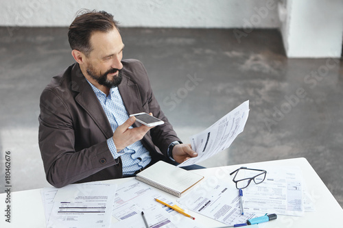 Garden Poster Hard working male enterpreneur makes voice call on smart phone, explains how to make business project, looks at document, sits in his cabinet. People, career, business, success, modern technologies