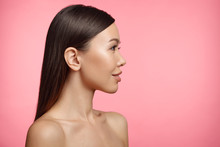 Sideways Portrait Of Naked Brunette Young Female With Healthy Skin, Looks Aside, Isolated On Pink Background. Woman Wears No Clothes. Beauty, Health Concept. Adorable Girl Poses In Studio. Feminity
