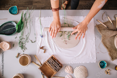 Leinwand Poster female potter master rolling up the clay on table with ceramic products