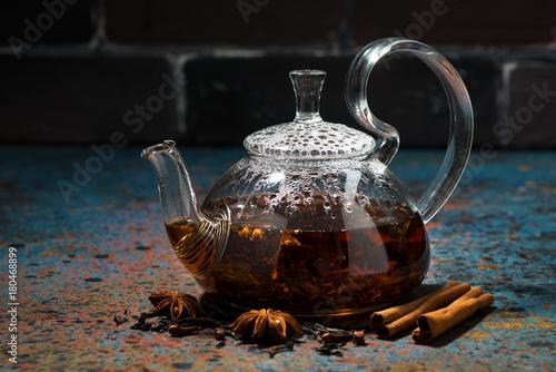 Fotografie, Obraz tea masala in a glass teapot on a dark background