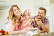 girl and her parents are eating vegetables and smiling while cooking in kitchen