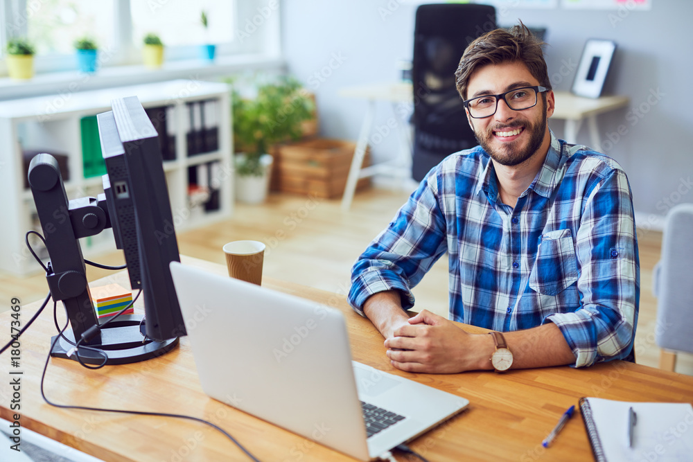Fototapeta Smiling young programmer staring straight at camera while sitting at his desk