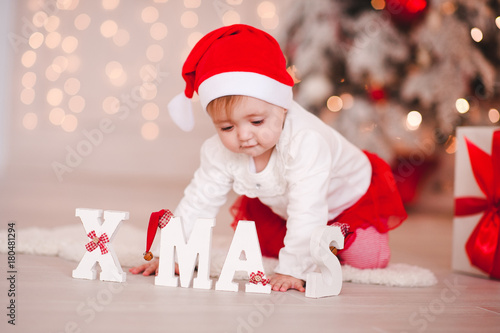 8de8267783 Cute baby girl wearing santa hat posing over Christmas background with xmas  letters. Focus on