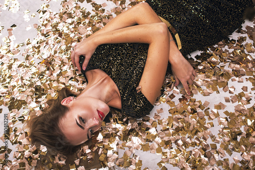 Photo  Top view of sexy young woman in black dress looking at camera while lying in con