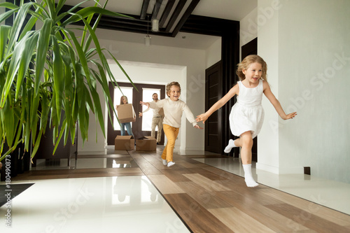 Fotografia Happy young family with cardboard boxes in new home at moving day concept, excit