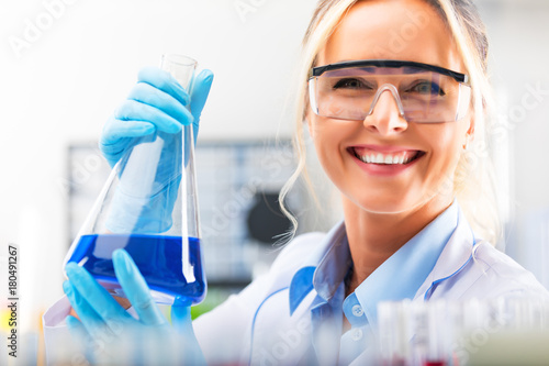 Fotografie, Obraz Young attractive female scientist holding a flask with blue liquid substance in