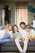 Family with children having fun using laptop sitting on sofa at home, parents and son daughter relaxing on couch holding computer, man woman with kids smiling watching funny video online, vertical