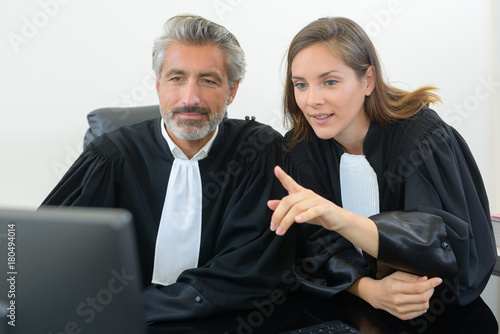 Fotografía lawyers looking at computer in court gowns