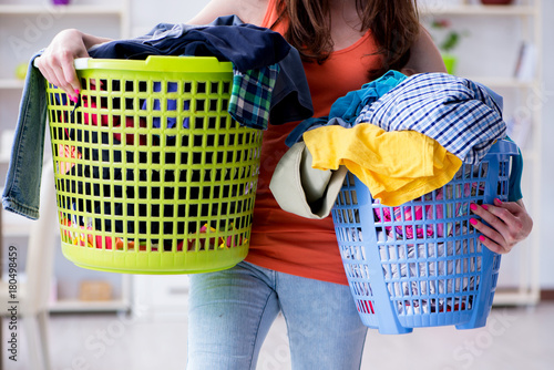 Fototapeta Stressed woman doing laundry at home