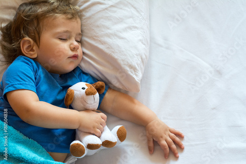 Obraz na plátně Cute baby boy sleeping on the bed at home with toy. Free space
