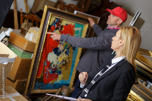 man holding and showing a painting to auctioneer before auction Canvas Print