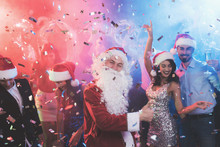 A Man Dressed As Santa Claus Has Fun At A New Year Party. Together With Him Have Fun Friends.