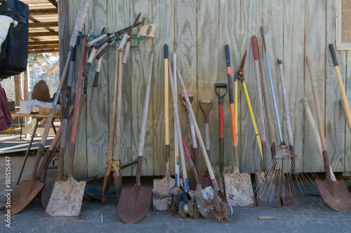 A Variety Of Used Garden Tools For Sale At A Flea Market Near