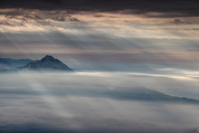 Curtain Of Sun Rays Shining Through Dark Gray Clouds Illuminates Two Conical Mountains In Autumn Morning Mist, Storzic And Tolsti Vrh Peaks, Kamnik Savinja Alps, Gorenjska, Carniola, Slovenia, Europe