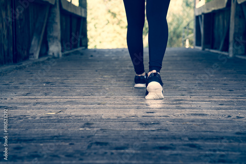 Fotografie, Obraz  Young sporty woman stepping forward on a wooden bridge, low to the ground view