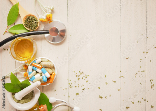 herbal alternative medicine  with capsule, stethoscope, beaker mortar on wood background Canvas Print