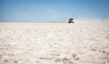 A Four Wheel Drive Vehicle Driving Over The Salt Pans In Botswana
