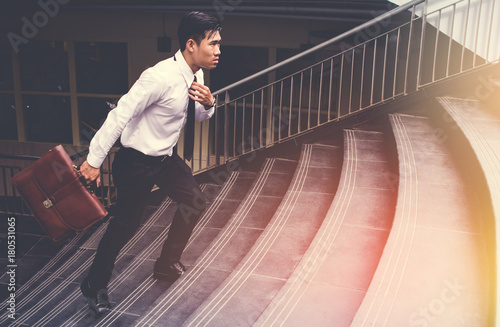 Young Asian Businessman Holding Brown Leather Bag Working On