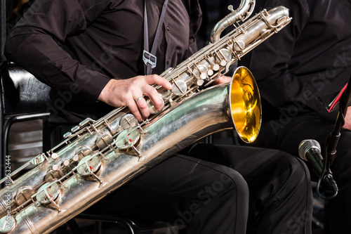 The saxophonist of the jazz collective sits on a chair and puts a baritone saxophone on his knees Canvas Print