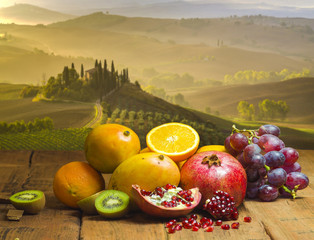 Fototapeta Owoce fruits on a wooden table, in the background the landscape of Italian Tuscany