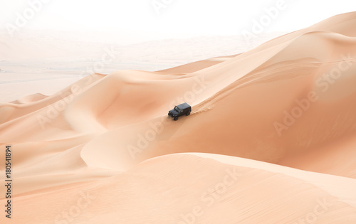 Poster Abou Dabi A single black car scaling giant sand dunes in the Empty Quarter desert. Abu Dhabi, UAE.