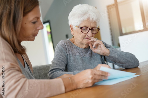 Fotomural  Home assistant helping elderly woman with paper work