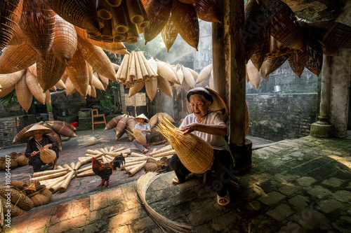 Photo  Old Vietnamese female craftsman making the traditional bamboo fish trap or weave