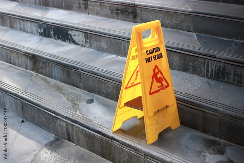 Cuadros en Lienzo Yellow caution wet floor sign at staircase of outdoor city.