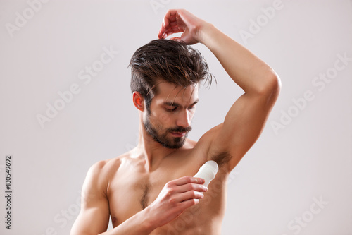 Photo Young man is applying roll on antiperspirant to his armpit.