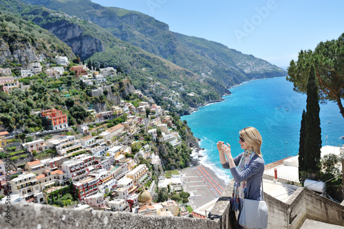 Tourist taking photos with cell phone in Positano, Amalfi coast, Italy