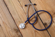 Closeup of a medical stethoscope, isolated on wooden background