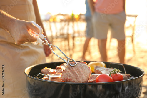 In de dag Buffet, Bar Man cooking steaks and vegetables on barbecue grill, outdoors
