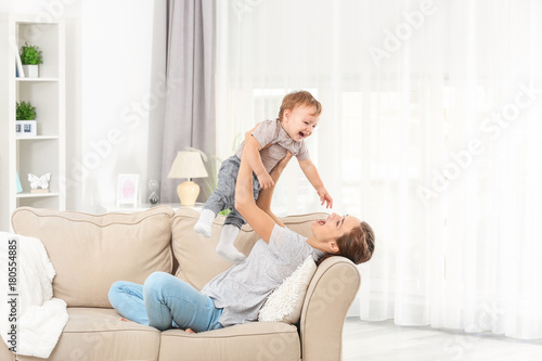 Obraz Mother with baby boy on sofa at home - fototapety do salonu