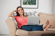 Young woman with modern laptop on sofa at home
