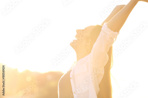 Fotografia  Excited woman raising arms at sunset