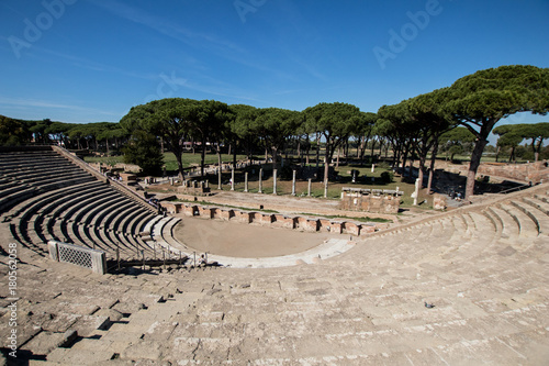 Foto op Plexiglas Oude gebouw Almost complete Roman theater in Ostia antica. Drama place in ancient Rome with sea pines in background and ruins