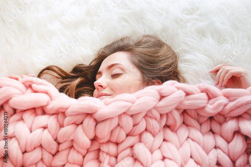 Fotografie, Obraz  Young woman sleeping under warm peach color throw blanket