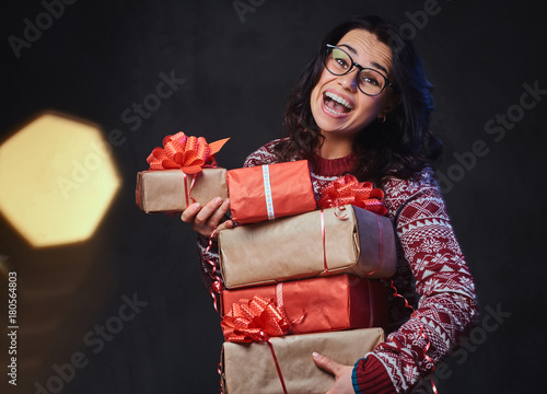 A woman holds Christmas gifts.