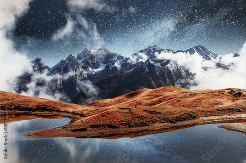 Poster Bergen Fantastic starry sky on mountain lake Koruldi. Picturesque night Upper Svaneti, Georgia Europe. Caucasus mountains