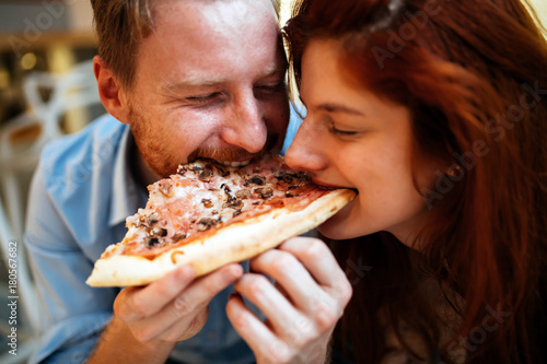 In de dag Kruidenierswinkel Couple sharing pizza and eating