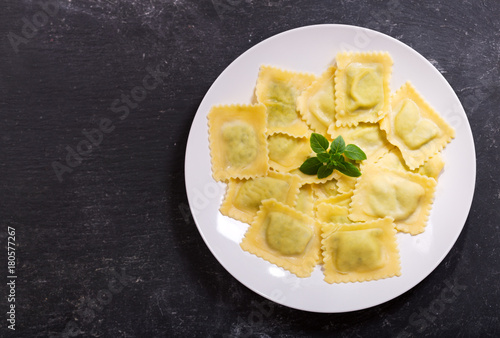 plate of ravioli with basil on dark background