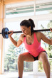 Pretty woman in sportswear holding barbell on her shoulders, lifting it