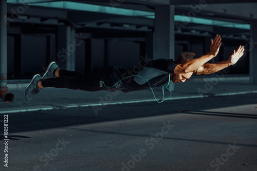 Fotografía  Young man doing push ups with jumps in the urban environment
