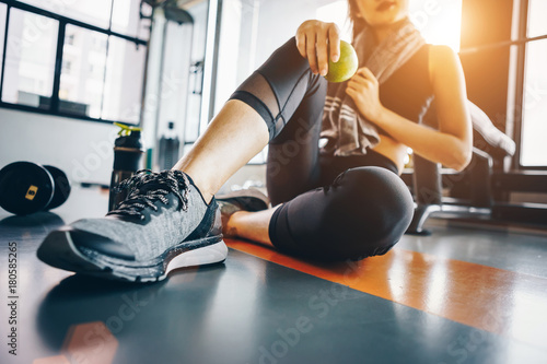 Deurstickers Fitness Asian woman exercising in the gym, Young woman workout in fitness for her healthy and office girl lifestyle. She is holding green apple.