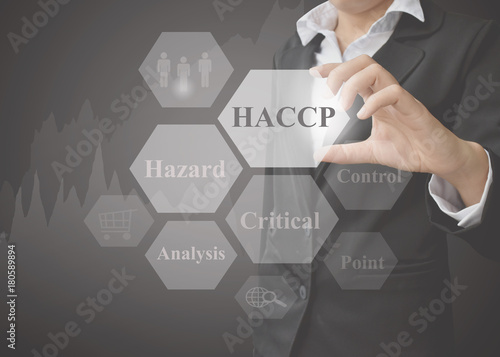 Fotografía  Business woman showing presentation of meaning of HACCP concept (Hazard Analysis of Critical Control Points) a principle on black background for use in business, company system and training