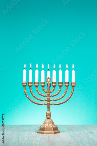 Fotografie, Obraz Bronze Hanukkah menorah with burning candles on wooden table front old vintage aquamarine wall background