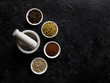 Indian Spices on a Black Background. With A White Mortar And Pestle.