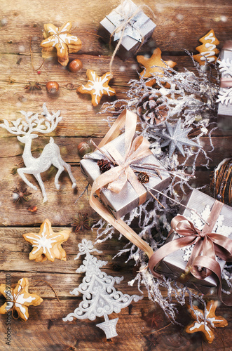 Fototapety, obrazy: Christmas wreath with ginger cookies, silver stars, cones, hazelnut, anise, tape, ribbon, snowflakes, reindeer. Top view, copy space, light bokeh, snow effect, toned