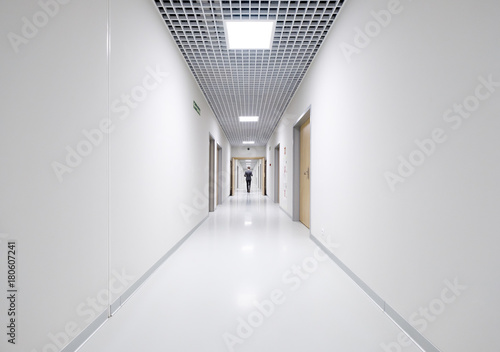 Business man back view at long white empty corridor interior Canvas Print